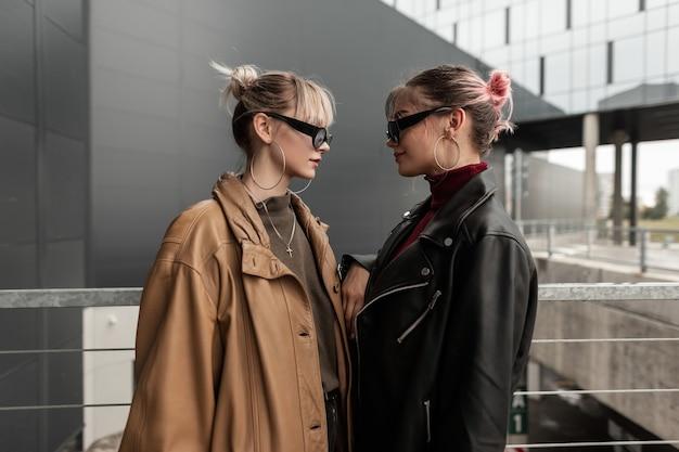 Ritratto di moda di due belle giovani donne in elegante giacca di pelle con occhiali da sole che si guardano in città