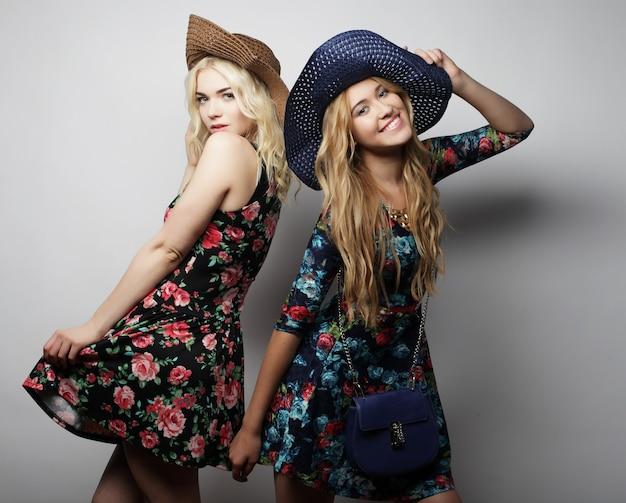 Moda ritratto di due ragazze alla moda migliori amiche, indossando abiti e cappelli. tempo felice per il divertimento.
