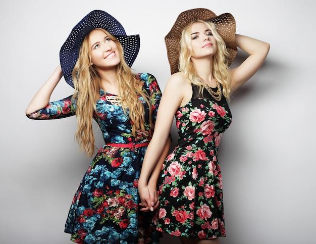 Moda ritratto di due migliori amiche ragazze alla moda, indossando abiti e cappelli.