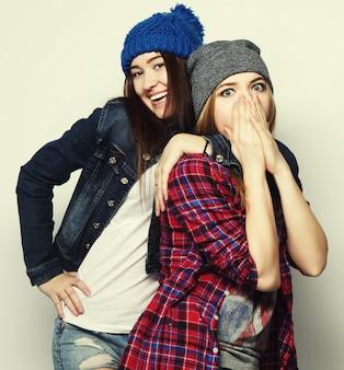 Moda ritratto di due migliori amiche di ragazze hipster sexy alla moda, indossando abiti e cappelli carini. su sfondo grigio.