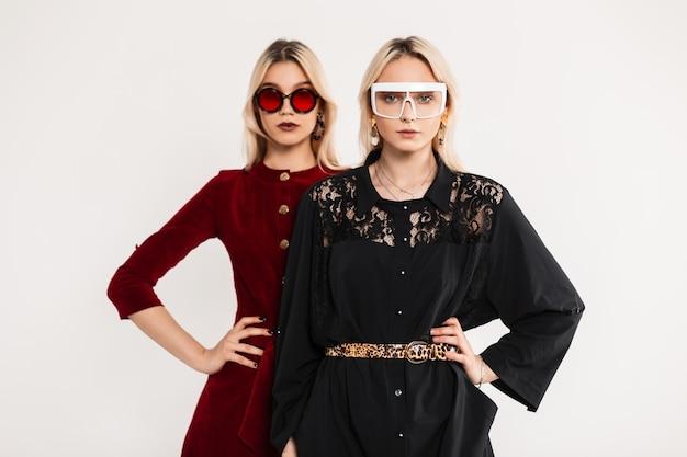 Moda ritratto due amiche adolescenti in occhiali da sole giovanili colorati alla moda in abiti rosso-neri vicino al muro vintage grigio