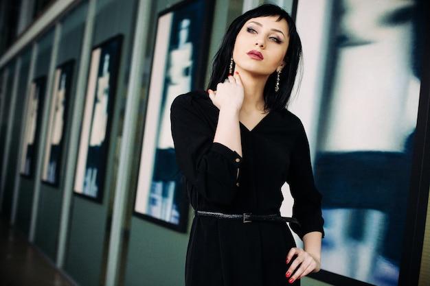 Moda ritratto di giovane bella donna in abito nero.