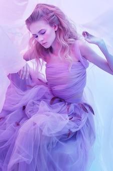 Adatti il ritratto di giovane bella donna in vestito viola lanuginoso. capelli ricci biondi, trucco, vestito con piume, colori tenui, foto d'arte