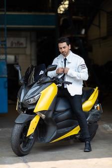 Ritratto di moda giovane bel ragazzo in posa su una moto