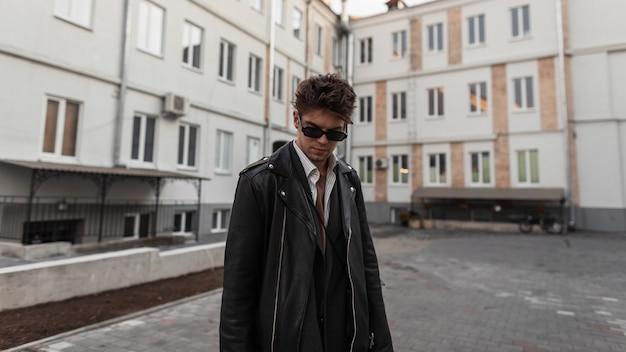 Moda ritratto di un giovane hipster in occhiali da sole con un'acconciatura alla moda in giacca di pelle nera alla moda vicino a edifici in città in strada. modello di moda europeo bel ragazzo in posa all'aperto.