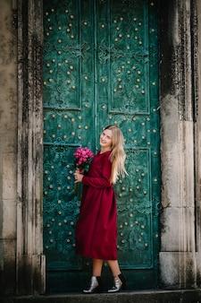 Adatti il ritratto di giovane donna alla moda della signora con il mazzo di fiori che cammina per strada, che porta vestito alla moda carino, bella ragazza in un vestito rosso che sorride gode dei suoi fine settimana.