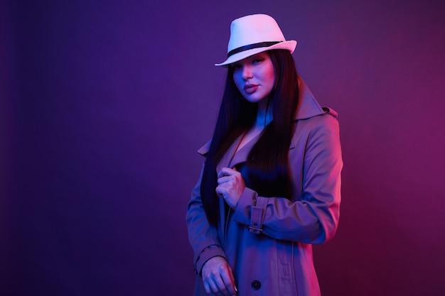 Moda ritratto di giovane donna in un cappotto e un cappello in studio con filtri colorati. concetto di moda al neon.