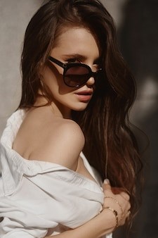 Moda ritratto di una giovane donna in occhiali da sole alla moda in posa all'aperto in una giornata di sole estivo