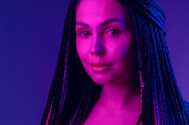 Moda ritratto di giovane donna con i dreadlocks alla luce al neon