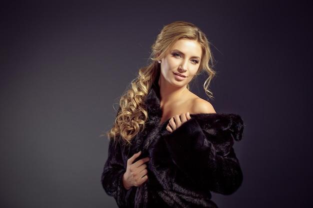 Moda seducente signora capelli biondi in un elegante cappotto di pelliccia e biancheria intima nera