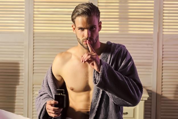 Moda uomo sexy spettacolo silenzio gesto dito segreto in bagno Foto Premium