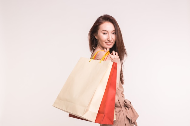 Concetto di moda, shopping e persone - felice donna bruna con sacchi di carta dopo lo shopping su bianco