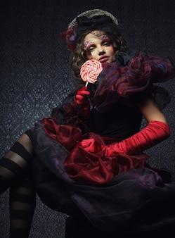 Colpo di moda di donna in stile bambola. trucco creativo. abito fantasia.