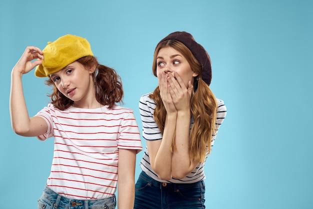 Sorelle di moda in cappelli divertimento studio sfondo blu stile di vita