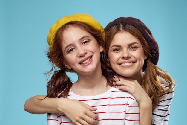 Sorelle di moda in cappelli divertimento sfondo blu di stile di vita