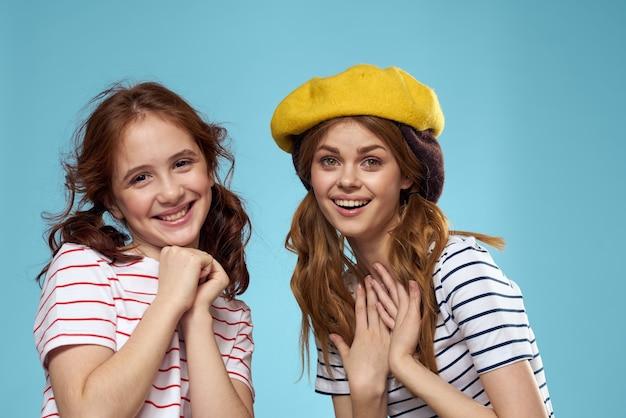 Sorelle di moda in cappelli divertimento studio parete blu stile di vita Foto Premium