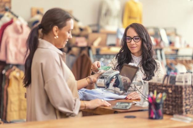 Il cliente del negozio di moda paga i suoi acquisti con un pagamento senza contatto con carta.