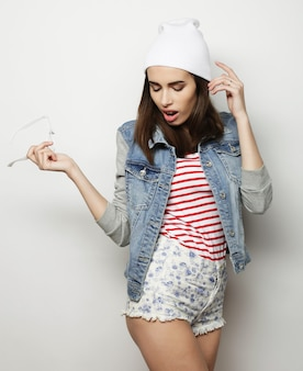 Ritratto in studio di moda di bella giovane donna bruna che indossa outfit hipster