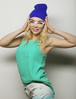Ritratto in studio di moda di una donna bionda hipster piuttosto giovane con gli occhiali, che indossa una maglietta e un cappello urbani alla moda, su sfondo bianco