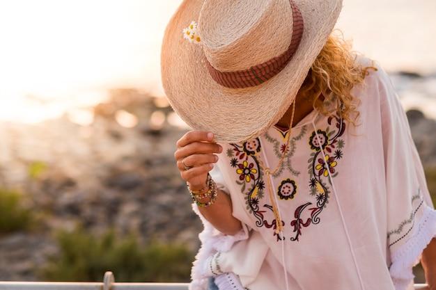 Vestiti alla moda e irriconoscibile donna caucasica nascosta dal cappello da cowboy per le vacanze - concetto di viaggio e vacanza estiva con spiaggia sfocata in una giornata di sole