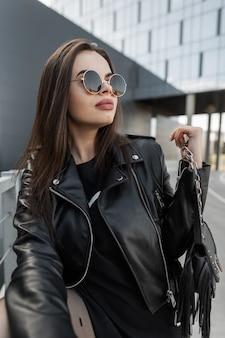 Moda elegante bella donna modello in occhiali da sole rotondi vintage con giacca di pelle alla moda e abito nero con borsa alla moda passeggiate in città