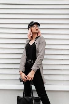 Moda elegante bella giovane donna con occhiali e un cappello in abiti casual alla moda con una borsa alla moda si trova vicino a una parete di legno