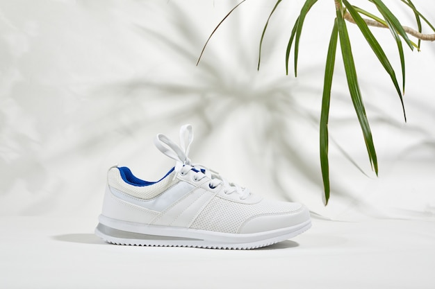 Moda sneaker alla moda e ombra di foglie di palma su un muro bianco. uomini che eseguono scarpe sportive con tonalità monocromatiche astratte di piante o alberi.
