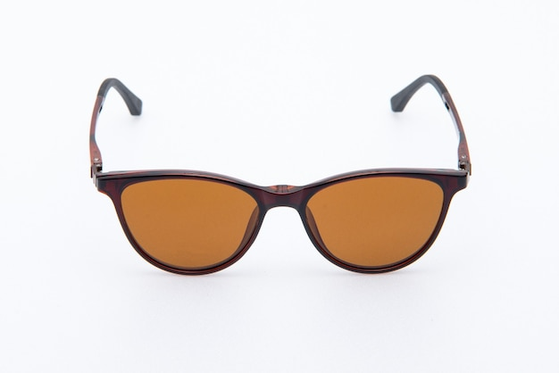 Occhiali da sole moda montature marroni e lenti arancioni su sfondo bianco