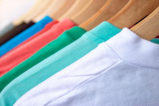 T-shirt di moda su stendibiancheria - primo piano dell'armadio colorato luminoso su portabiti in legno nell'armadio del negozio.