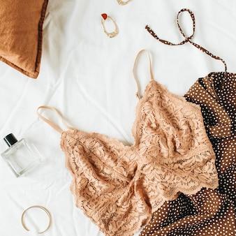 Composizione di biancheria intima alla moda di moda. reggiseno, profumo, abito da sera su lino bianco