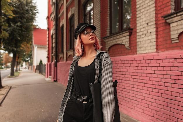 Moda urbana bella ragazza con capelli rosa in abiti di moda, una camicia e jeans con occhiali e un berretto vintage sta camminando per strada vicino a un edificio in mattoni del grunge