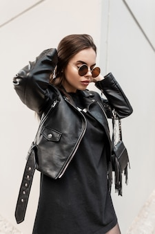 Moda ritratto urbano di una bella donna in stile rock nero con eleganti occhiali da sole su sfondo grigio. bellezza e stile femminile casual