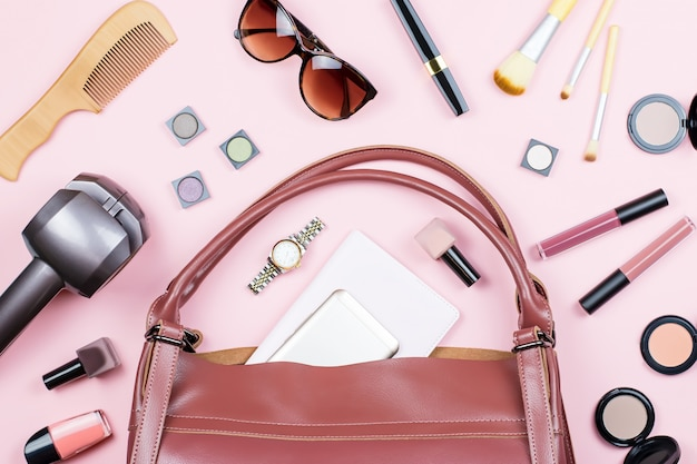 Collezione di accessori moda donna. roba da borsa, prodotti di bellezza, bigodino di capelli, smartphone, blocco note, borsa.