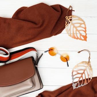 Moda donna borsa e sciarpa, accogliente abbigliamento femminile autunno decorato foglie d'autunno.