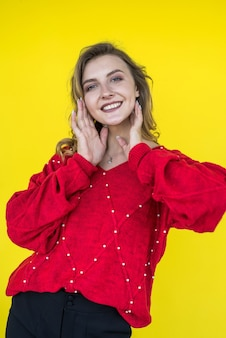 Moda donna in maglione lavorato a maglia rosso classico in posa e sorridente su sfondo giallo. stile di vita