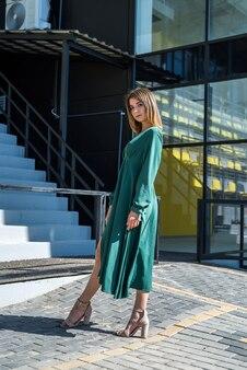 Moda donna in abito verde vicino a un edificio moderno in vetro. elegante ritratto femminile