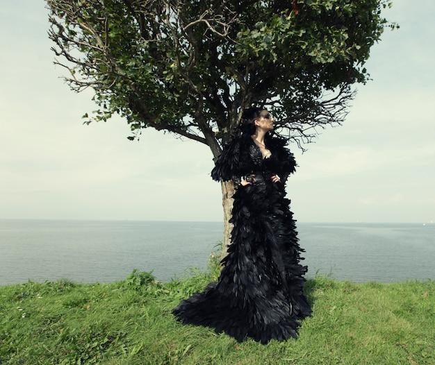 Moda donna in posa vicino al mare. regina oscura.