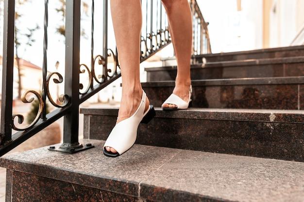 Moda donna con belle gambe in eleganti sandali in pelle estivi scende le scale in città. avvicinamento.