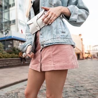 Moda donna con borsa alla moda in giacca di jeans e gonna rosa che cammina in città