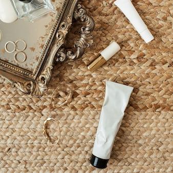Accessori moda donna e cosmetici. vassoio, profumo, correttore, rossetto, anelli, orecchini su paglia