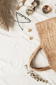 Accessori moda donna, borsa di paglia, cuscino, rami di eucalipto su lino bianco