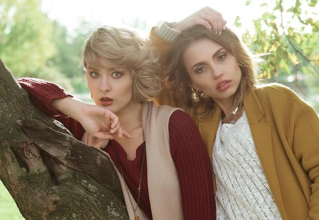 Donne di moda in posa insieme all'aperto, parco autunnale.