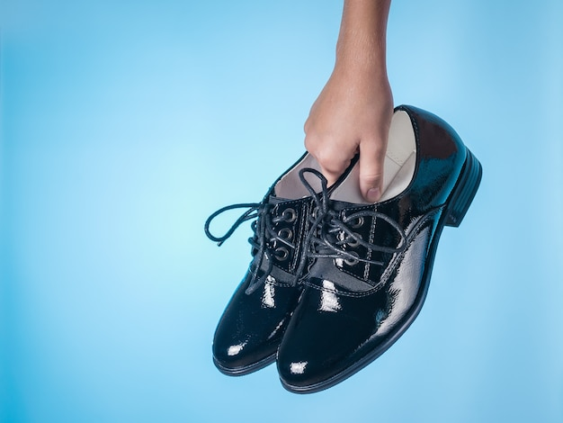 Moda scarpe da donna con lacci in mano del bambino sulla superficie blu. scarpe da donna in pelle eleganti e alla moda.