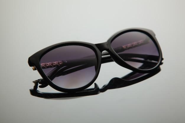 Occhiali da sole moda donna, plastica nera, decoro oro sulla doccia, elegante sfondo sfumato con filtro polarizzante.