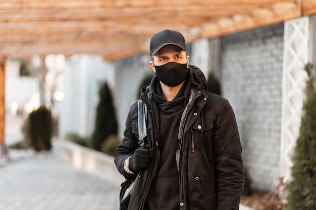 Moda giovane bell'uomo con una maschera protettiva nera in abiti alla moda con una giacca invernale, pullover ed elegante berretto nero con zaino per strada. concetto di coronavirus
