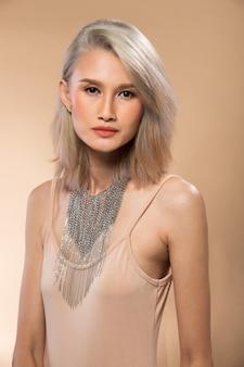 Moda giovane donna asiatica sottile argento grigio capelli belli compongono moda costumi da bagno in posa attraenti accessori look glam. studio lighting beige giallo crema sfondo, estate spiaggia calda sun