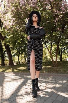Moda giovane donna in abito vintage nero in bellissimo cappello alla moda in giacca di pelle alla moda con stivali si trova nel parco sullo sfondo di alberi lilla. affascinante ragazza in abbigliamento elegante all'aperto in una giornata di sole.