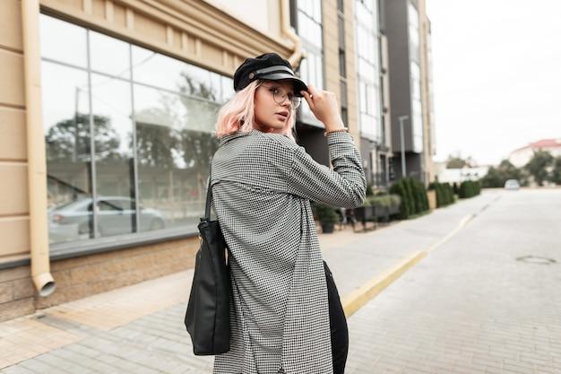 Modello di moda giovane donna in occhiali alla moda con un cappello vintage in una camicia a quadri alla moda con una borsa cammina per strada vicino all'edificio