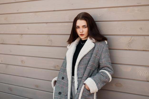 Moda giovane donna in elegante capispalla con cappotto vintage si trova pulito su uno sfondo di legno