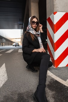 Moda giovane donna in occhiali da sole in elegante sciarpa di seta sulla testa in elegante cappotto nero in jeans con stivali in posa seduto sull'asfalto vicino alla colonna a strisce rosso-bianco in città. modello di ragazza d'affari.